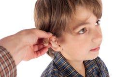 Sluit omhoog van een Audiologist ` s gehoorapparaat van de handmontage aan een jonge jongen royalty-vrije stock afbeelding