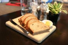 Sluit omhoog van een bakker die het enkel teruggetrokken brood tonen stock foto