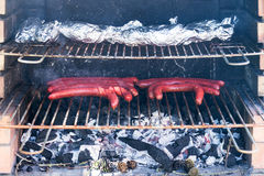 Sluit omhoog van een barbecue met worsten en folieaardappelen in de schil op een grill Royalty-vrije Stock Afbeelding