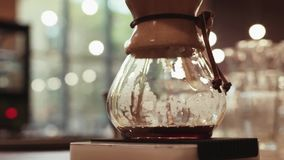 Sluit omhoog van een barista makend hand gebrouwen koffie Het toevoegen grinded koffie en gietend warm water Baristasportret binn stock video