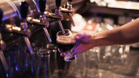 Sluit omhoog van een barman gietend bier en het halen van een dienblad met glazen stock videobeelden