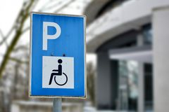 Sluit omhoog van een blauw gehandicapt de vergunningsteken van het persoonsparkeren op straat royalty-vrije stock fotografie