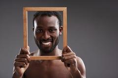Sluit omhoog van een blije knappe mens die een fotokader houden royalty-vrije stock afbeelding