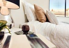 Sluit omhoog van een boek naast glas en een lamp op de lijst dichtbij aan Royalty-vrije Stock Foto