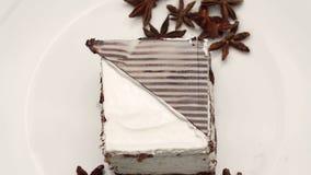 Sluit omhoog van een cake met slagroom en steranijsplant op witte plaat stock videobeelden