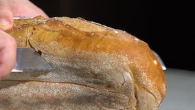 Sluit omhoog van een chef-kok met een groot mes om een brood van brood langzame motie te snijden stock videobeelden