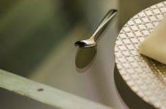 Sluit omhoog van een chroomlepel met een verzilverd tafelgerei aan één kant op een transparante glaslijst stock afbeelding