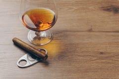 Sluit omhoog van een Cubaanse sigaar op een snijder van de roestvrij staalsigaar en een cognacglasglas brandewijn royalty-vrije stock foto's