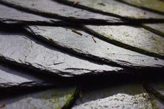 Sluit omhoog van een dak met oude steentegels die wordt behandeld stock fotografie
