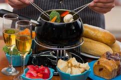 Sluit omhoog van een gastronomisch Zwitsers fonduediner met geassorteerde kazen en een verwarmde pot van kaasfondue, mensenholdin royalty-vrije stock foto