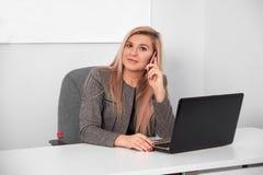 Sluit omhoog van een geinteresseerde onderneemster in een kostuum die op haar wit kantoor werken Zij spreekt op telefoon en het w royalty-vrije stock fotografie