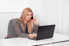 Sluit omhoog van een geinteresseerde onderneemster in een kostuum die op haar wit kantoor werken Zij spreekt op telefoon en het w royalty-vrije stock afbeelding