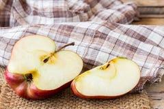 Sluit omhoog van een gesneden rode appel op een houten lijst Stock Afbeelding