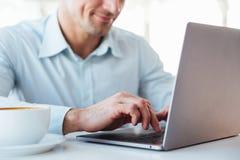 Sluit omhoog van een glimlachende rijpe mens gebruikend laptop computer stock afbeelding