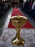 Sluit omhoog van een gouden miskelk vóór massa met een rood tapijt in de achtergrondkerkgemeenschapkop stock afbeelding