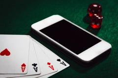 Sluit omhoog van een groene pooklijst met een smartphone, kaarten en dobbelt Winnend online geld stock foto's