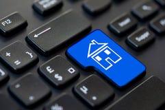 Sluit omhoog van een groene terugkeersleutel met een pictogram van een huis op computer Stock Foto