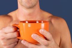 Sluit omhoog van een hand van de mens die een oranje koffiekop op blauwe achtergrond houden royalty-vrije stock foto