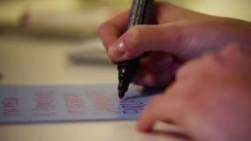 Sluit omhoog van een hand van de vrouwenschrijver schrijvend in een notitieboekje thuis RUW videoverslag stock video