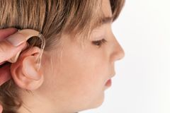 Sluit omhoog van een hand opnemend een gehoorapparaat in een jongens` s oor Stock Afbeelding