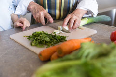Sluit omhoog van een hogere dame scherpe groenten op een raad stock afbeelding