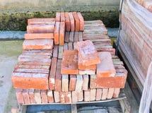Sluit omhoog van een houten palletovervloed van oude gestapelde rode bakstenen De bakstenen worden bevolen in vele rijen royalty-vrije stock foto