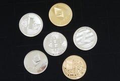 Sluit omhoog van een inzameling van zilveren en gouden crypto muntstukken stock afbeelding