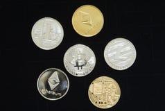Sluit omhoog van een inzameling van zilveren en gouden crypto muntstukken stock afbeeldingen