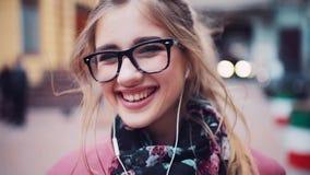 Sluit omhoog van een jong leuk meisje die met hoofdtelefoons charmingly net naar de camera, toevallig kapsel glimlachen Mooi stock video