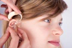 Sluit omhoog van een jonge girl& x27; s hoofd en audiologist& x27; s overhandigt inse royalty-vrije stock foto's