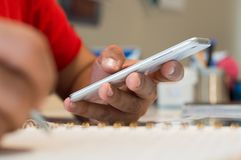 Sluit omhoog van een jonge mensenhand gebruikend mobiele slimme telefoon in het bureau stock afbeeldingen
