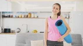 Sluit omhoog van een jonge mooie vrouw gekleed in blauwe jogging of een geschiktheidsmat na het werken thuis in de woonkamer stock footage