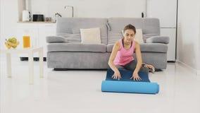 Sluit omhoog van een jonge mooie vrouw gekleed in blauwe jogging of een geschiktheidsmat na het werken thuis in de woonkamer stock video