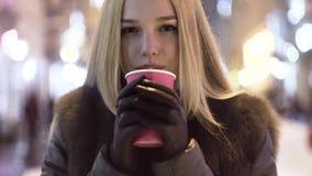Sluit omhoog van een jonge vrouw het drinken koffie bij een straat van de nachtstad Vage lichten op de achtergrond stock footage