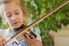 Sluit omhoog van een kind het spelen viool op groene achtergrond Portret van meisje met koord en het spelen viool Portret van wei royalty-vrije stock afbeeldingen