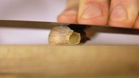 Sluit omhoog van een kruidnagel van knoflook die op een houten hakbord met een messenblad worden verpletterd stock video