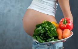 Sluit omhoog van een leuke zwangere buikbuik en een gezond voedsel Stock Afbeeldingen