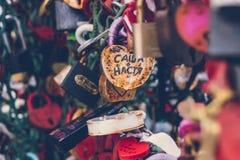 Sluit omhoog van een liefdeslot op een traliewerk op een slotenbrug met andere sloten vaag om een bokehachtergrond tot stand te b stock afbeeldingen