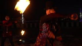 Sluit omhoog van een mannelijke uitvoerder in een kostuum, spinnen aangestoken op brandballen op kettingen, op de straat, langzam stock footage