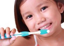Sluit omhoog van een meisje dat haar tanden borstelt stock afbeelding