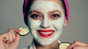 Sluit omhoog van een meisje met een masker op haar gezicht en een handdoek op haar hoofd dat haar ogen met komkommers sluit en gl stock videobeelden