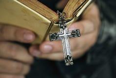 Sluit omhoog van een mens die een bijbel met dwars het hangen godsdienst en geloofsconcept lezen stock afbeelding