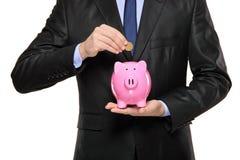 Sluit omhoog van een mens die een muntstuk opneemt in een bank Stock Fotografie