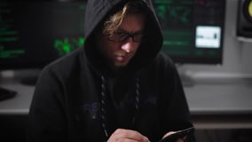 Sluit omhoog van een mens met een kap met oogglazen gebruikend zijn smartphone De Cyberspion binnendringt in een beveiligd comput stock videobeelden