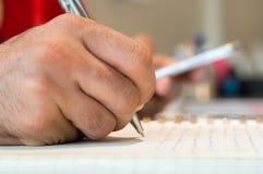 Sluit omhoog van een mensenhand schrijvend op zijn notitieboekje terwijl het houden van een mobiele slimme telefoon royalty-vrije stock fotografie