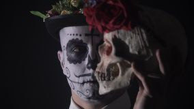 Sluit omhoog van een Mexicaanse Santa Muerte-mens met verf op zijn gezicht die een schedel 4k houden stock video