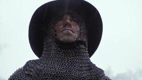 Sluit omhoog van een middeleeuwse militair in chainmailpantser met een zwaard in de regen stock footage