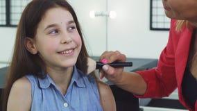 Sluit omhoog van een mooi meisje die terwijl haar mamma die make-up op haar gezicht toepassen glimlachen stock videobeelden