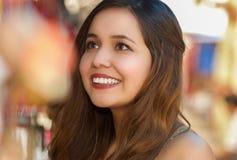 Sluit omhoog van een mooie glimlachende jonge vrouw die een kleurrijke Andes traditionele kunst, in kleurrijke marktstoffen kijke Stock Afbeeldingen
