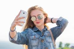 Sluit omhoog van een mooie jonge vrouw die een selfie op smartphone nemen openlucht stock foto's